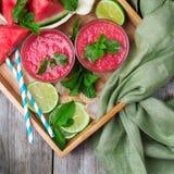 Fatias e bebida da melancia em uma tabela de madeira rústica Fotos de Stock