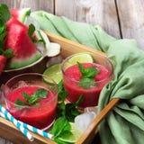 Fatias e bebida da melancia em uma tabela de madeira rústica Foto de Stock Royalty Free