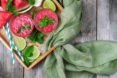 Fatias e bebida da melancia em uma tabela de madeira rústica Foto de Stock