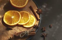 Fatias e canela alaranjadas na tabela Foto de Stock Royalty Free