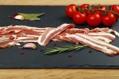 Fatias, especiaria e tomate crus do bacon na placa preta fotos de stock royalty free