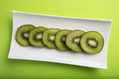 Fatias frescas do fruto de quivi do corte em uma placa Imagens de Stock
