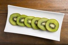 Fatias frescas saudáveis do fruto de quivi do corte em uma placa Imagens de Stock Royalty Free