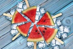 Fatias frescas, suculentas e saborosos de melancia no gelo e em uma superfície de madeira azul fotografia de stock royalty free
