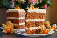 Fatias grandes de bolo de cenoura fresco com o physalis como a decoração e de uma cesta das flores Fotografia de Stock Royalty Free