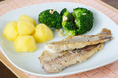 Fatias lisas de peixes grelhados com batatas e brócolos Foto de Stock