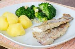 Fatias lisas de peixes grelhados com batatas e brócolos Foto de Stock Royalty Free