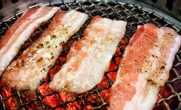 Fatias postas de conserva Yakiniku da barriga de carne de porco do japonês em uma grade de carvão fotografia de stock