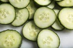 Fatias saudáveis do pepino do corte da vista macro no fundo branco Fotos de Stock