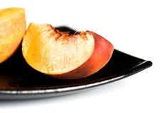 Fatias vermelhas dos pêssegos no prato preto Fotografia de Stock