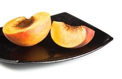 Fatias vermelhas dos pêssegos no prato preto Fotografia de Stock Royalty Free