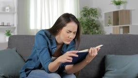 Fatiga visual sufridora de la mujer que lee un libro almacen de video