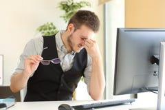 Fatiga visual sufridora del hombre de negocios en la oficina fotografía de archivo