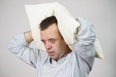 Fatigué somnolent d'homme avec l'oreiller sur le gris image stock