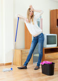 Fatigue long-haired woman washing floor with mop Stock Image