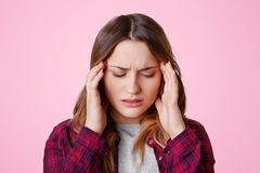 Fatigue overworked stressful female model keeps hands on temples, suffers from terrible headache, closes eyes, feels pain, wears c. Asual checkered shirt Royalty Free Stock Images