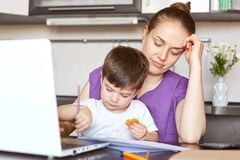 Fatigue overworked young female enterpreneur involved in family business, tries to make financial report, takes care of child simu. Ltaniously, sit at kitchen Royalty Free Stock Photos