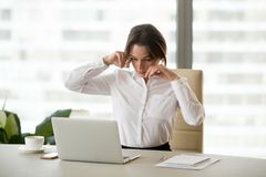 Fatigued businesswoman feeling tired of computer touching dry ir stock images