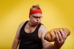 Funny fat man sweats while lifting burger. Fatigued funny fat man sweats while lifting burger Royalty Free Stock Photography