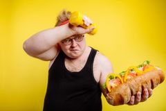 Fatigued fat man sweats while lifting burger. Fatigued funny fat man sweats while lifting burger Royalty Free Stock Images