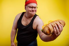 Funny fat man sweats while lifting burger. Fatigued funny fat man sweats while lifting burger Royalty Free Stock Images