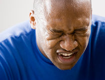 Fatigued man grimacing. Fatigued man dripping sweat and grimacing royalty free stock image