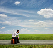 Fatigued man sitting on his bag. And looking forward stock photography