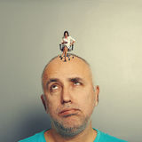 Fatigued man and small angry woman. Fatigued men and small angry women on his head over grey background stock images