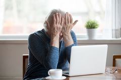 Fatigued senior man feeling tired from computer rubbing irritate. Fatigued senior mature man feels tired from computer rubbing dry irritated eyes to relieve pain stock image
