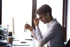 Fatigued utmattad affärsman som av tar exponeringsglas som känner ögonst royaltyfria foton