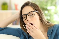 Fatigued woman yawning at home. Fatigued woman yawning covering the mouth with a hand at home stock photography