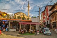 Fatih Mosque in Pristina. Pristina, Kosovo - July 29, 2014 Two men resting with coffee under Fatih Mosque located in the center of the old town witch is Royalty Free Stock Images