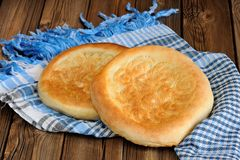 Fatir, uzbek flatbread on blue arab scarf on wooden background Stock Photography