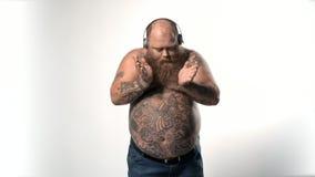 Fatso maschio che gode della canzone favorita dalle cuffie stock footage