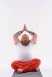 Fatso maschio che medita su stuoia Immagini Stock Libere da Diritti