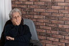 Fattig äldre kvinna som sitter på stol nära tegelstenväggen fotografering för bildbyråer