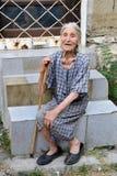 Fattig gammal bulgarisk kvinna med att gå rottingen och slitet ut, sjaskigt klänningsammanträde på trappa på gatan av Varna Royaltyfri Fotografi