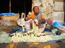 Fattig gammal kvinna som säljer blommor på marknaden Arkivfoto