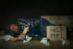 Fattig hög man som ligger nära papptecken för ATT HJÄLPA MIG royaltyfri bild