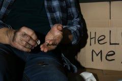 Fattig hög man som räknar mynt nära papptecken för ATT HJÄLPA MIG royaltyfria bilder