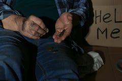 Fattig hög man som räknar mynt nära papptecken för ATT HJÄLPA MIG arkivfoton