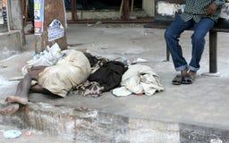 : Fattig indisk sömn för hög man i en hållplats på en upptagen väg Arkivfoton