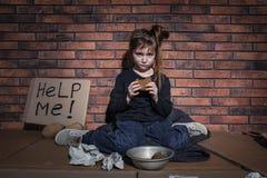 Fattig liten flicka med bröd och ATT HJÄLPA MIG att underteckna på golv nära väggen arkivbild