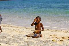 Fattig malagasy pojke som bryter kokosnötter på stranden arkivbild