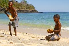 Fattig malagasy pojke som bryter kokosnötter på stranden royaltyfri foto