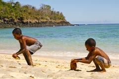 Fattig malagasy pojke som bryter kokosnötter på stranden arkivfoto