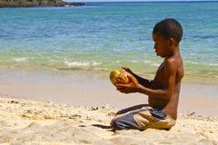 Fattig malagasy pojke som bryter kokosnötter på stranden royaltyfri fotografi