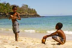 Fattig malagasy pojke som bryter kokosnötter på stranden arkivbilder