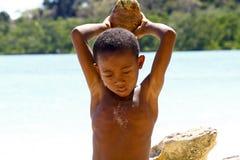 Fattig malagasy pojke som bryter kokosnötter på stranden royaltyfri bild