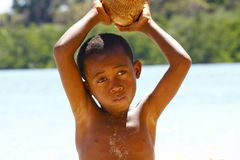 Fattig malagasy pojke som bryter kokosnötter på stranden royaltyfria foton
